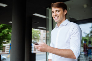 Portrait of cheerful young businessman using smarphone and smiling near business center
