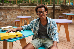 Portrait of cheerful young man in glasses sitting and smiling in outdoor cafe