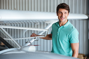 Portrait of cheerful young man pilot near small airplane
