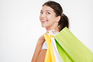 Portrait of cheerful young woman holding purchasings after shopping. Isolated over white background. Look at camera.