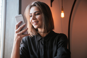 Portrait of cheerful young woman sitting at the table in cafe and chatting by her phone.