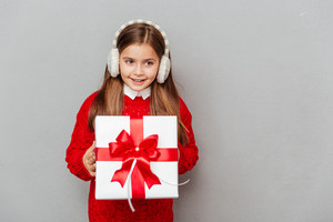 Portrait of cheerul little girl in red sweater and earmuffs with gift box