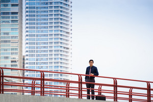 Portrait of chinese businessman standing and leaning on bridge in Panama. Skyscrapers in background