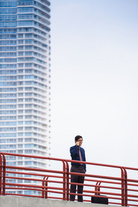 Portrait of chinese businessman standing on bridge in Panama city with skyline in background, answering phone call