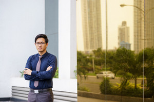 Portrait of chinese businessman standing with arms crossed near office building in Panama. Reflections of city on mirror