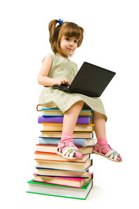 Portrait of clever girl sitting on books with laptop in front and typing