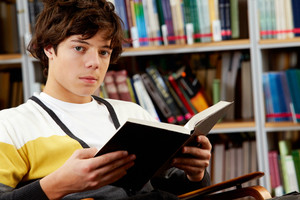 Portrait of clever student with open book reading in college library