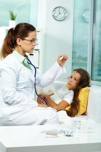 Portrait of clinician in eyeglasses looking at thermometer with sick girl lying near by
