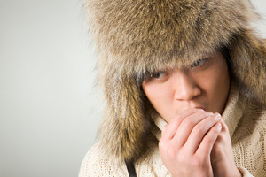 Portrait of cold man in fur hat and knitted sweater warming up his hands