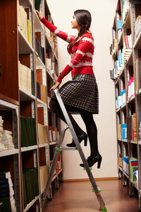 Portrait of college student choosing books in library