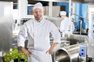 Portrait of confident and smiling chef making food in large kitchen