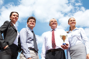 Portrait of confident business group on background of cloudy sky