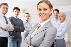 Portrait of confident business people looking at camera with pretty woman in front