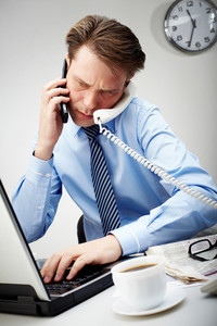 Portrait of confident businessman calling by two phones and typing simultaneously