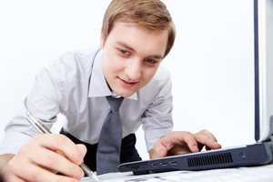 Portrait of confident businessman making notes with laptop near by