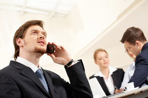 Portrait of confident businessman talking by cellphone with working team on background