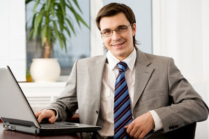 Portrait of confident businessman with glasses looking at camera and smiling