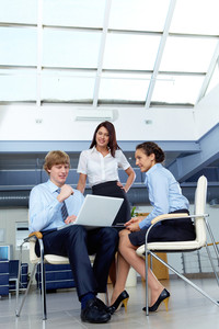 Portrait of confident businesswoman with businessman interviewing woman in the office