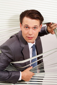 Portrait of confident man looking at camera out of venetian blind