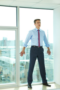 Portrait of confident man standing by the window in office