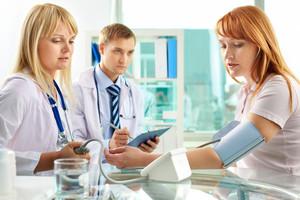 Portrait of confident practitioner measuring blood pressure in hospital