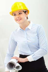 Portrait of confident woman in helmet holding blueprints
