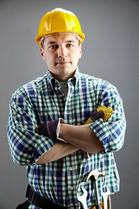 Portrait of confident worker in helmet isolated on grey