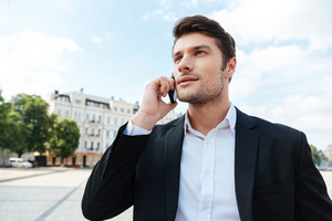 Portrait of confident young businessman talking on mobile phone outdoors