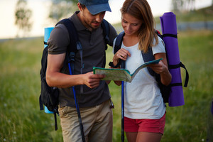 Portrait of couple of hikers looking at map in the countryside at summer