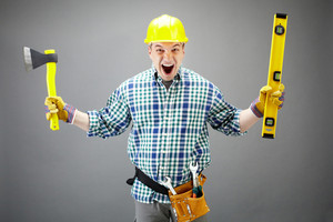 Portrait of crazy architect worker with axe and level measuring device