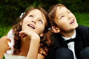 Portrait of cute boy groom and girl bride