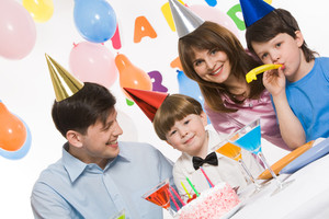 Portrait of cute boy having his birthday party with parents and elder brother surrounding him