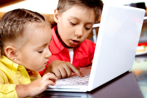 Portrait of cute children typing on laptop