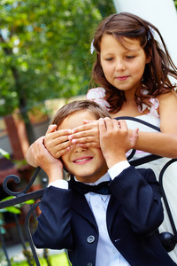 Portrait of cute girl bride shutting eyes of her groom by hands