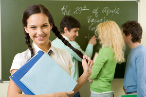 Portrait of cute girl holding textbook in hands on background of communicating students