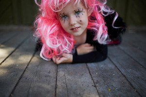 Portrait of cute girl in pink wig looking at camera