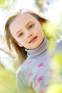 Portrait of cute girl looking at camera in natural environment