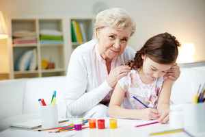 Portrait of cute girl making card for her mom with her grandmother near by