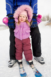 Portrait of cute girl wearing winter clothes while skiing with her father
