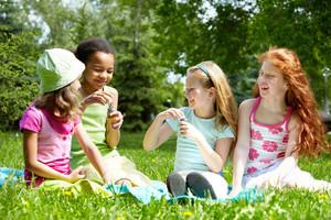 Portrait of cute girls having fun on green lawn in park