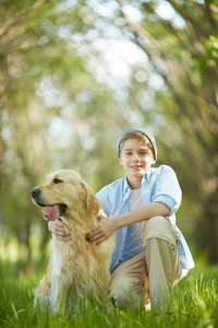 Portrait of cute lad embracing his white Labrador