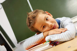 Portrait of cute lad looking at camera with his head on copybooks in classroom