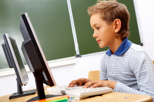 Portrait of cute lad typing on computer board in classroom