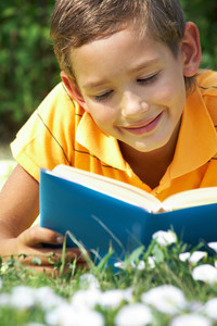 Portrait of cute schoolboy reading interesting book in natural environment