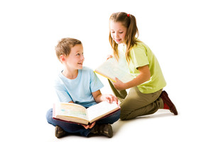 Portrait of cute schoolchildren holding open books and communicating