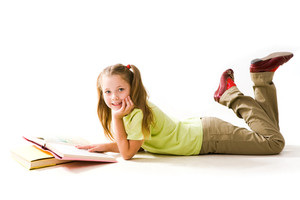 Portrait of cute schoolgirl keeping her hand on open book and looking at camera