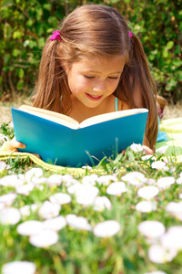 Portrait of cute schoolgirl reading interesting book in natural environment