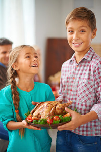Portrait of cute siblings with roasted turkey garnished with vegetables on plate