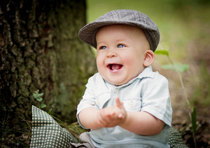 Portrait of cute smiling baby boy sitting in the forest