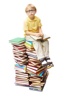 Portrait of diligent pupil sitting on top of books and looking at camera